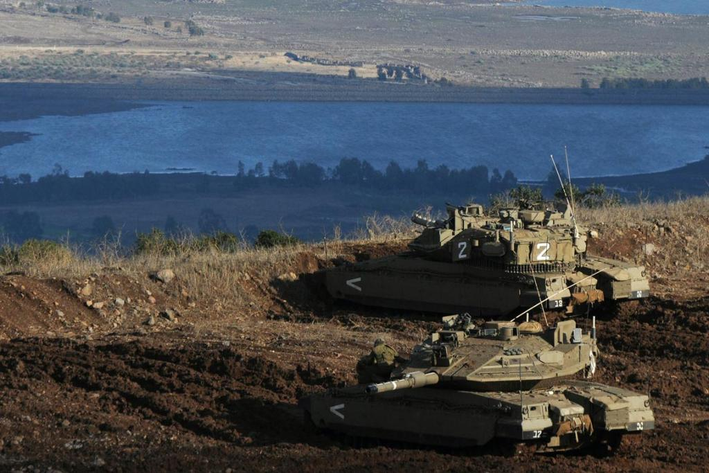 "Israeli tanks stand in position overlooking a Syrian village from the Israeli-occupied Golan Heights. Israel's army fired tank shells into Syria on Monday and scored ""direct hits"" in response to a Syrian mortar shell that struck the Israeli-occupied Golan Heights, the Israeli military said in a statement."