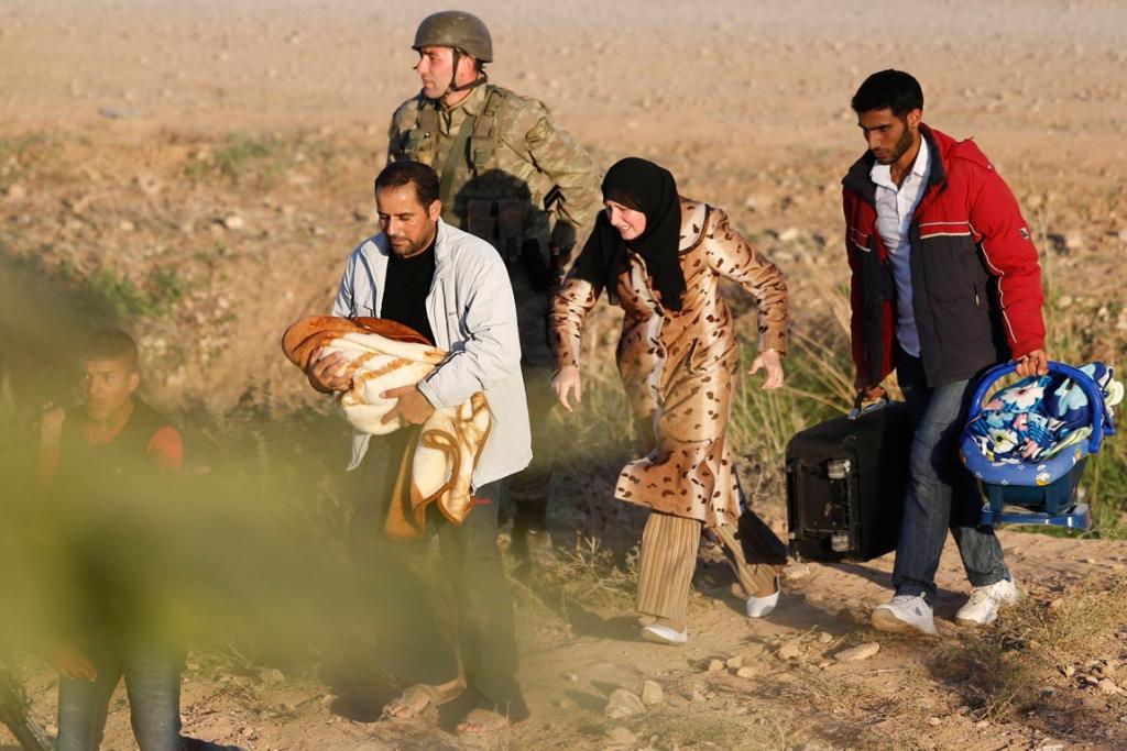 A Syrian family is escorted by a Turkish soldier after they crossed the border fences.