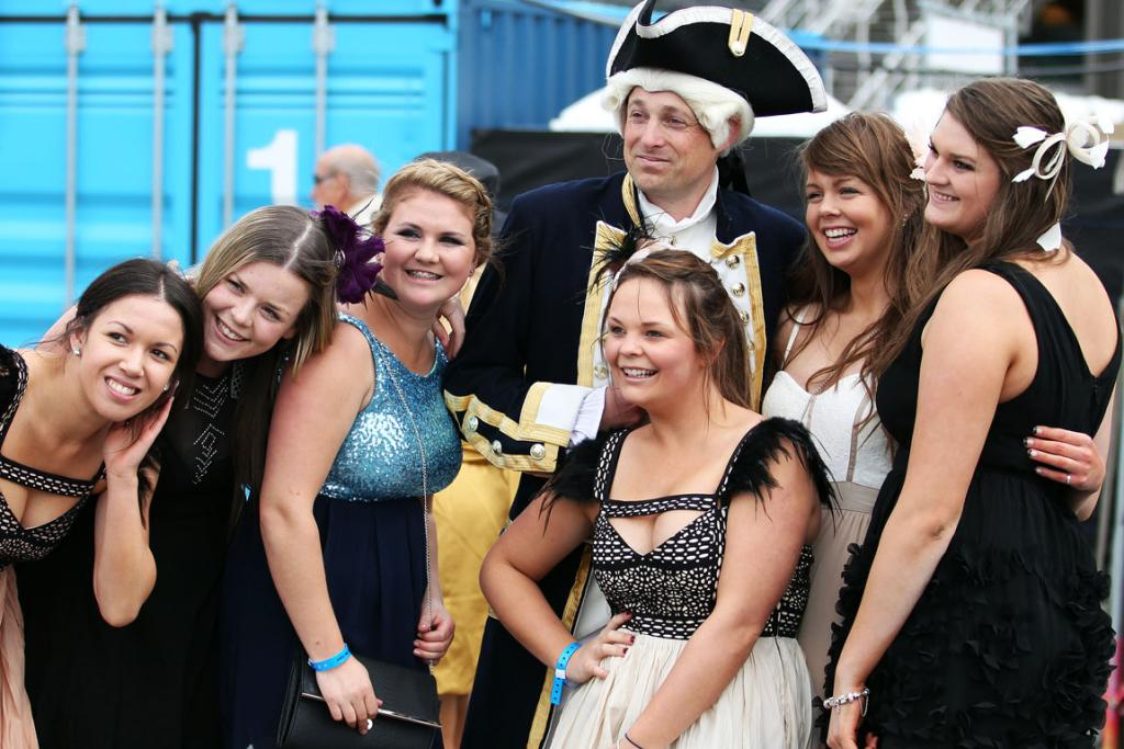 DRESSED UP: Ladies line up to get their photo taken with Michael Cooke dressed as Captain Cook early on Cup Day.