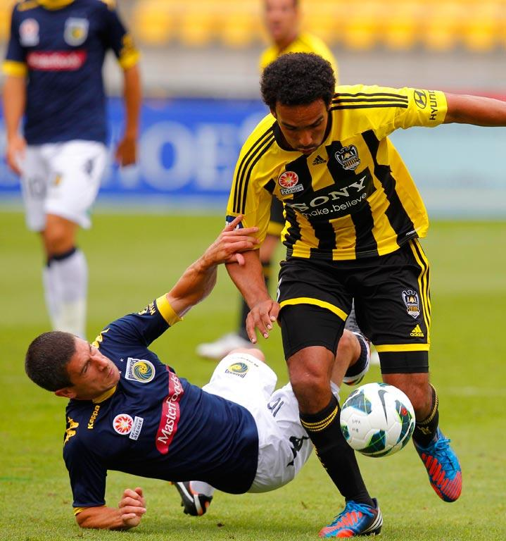 Paul Ifill of Wellington tackles Central Coast's Tomas Rogic.