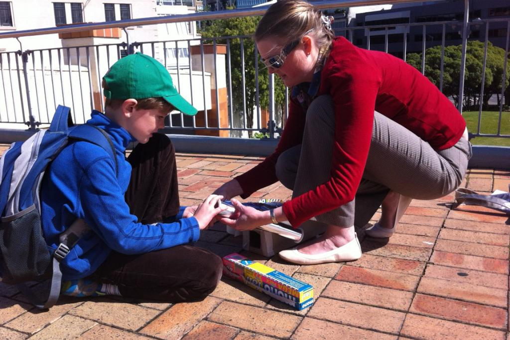 Alex Telfar, 8, and his mum Lucy build a pin hole camera to view the eclipse.