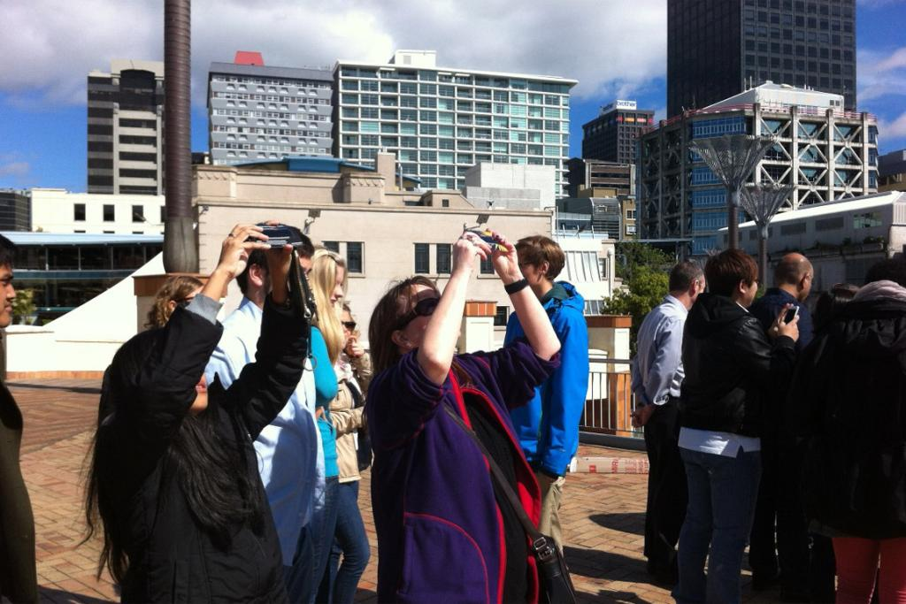 People in Wellington's Civic Square hold up special viewers to observe the partial solar eclipse.