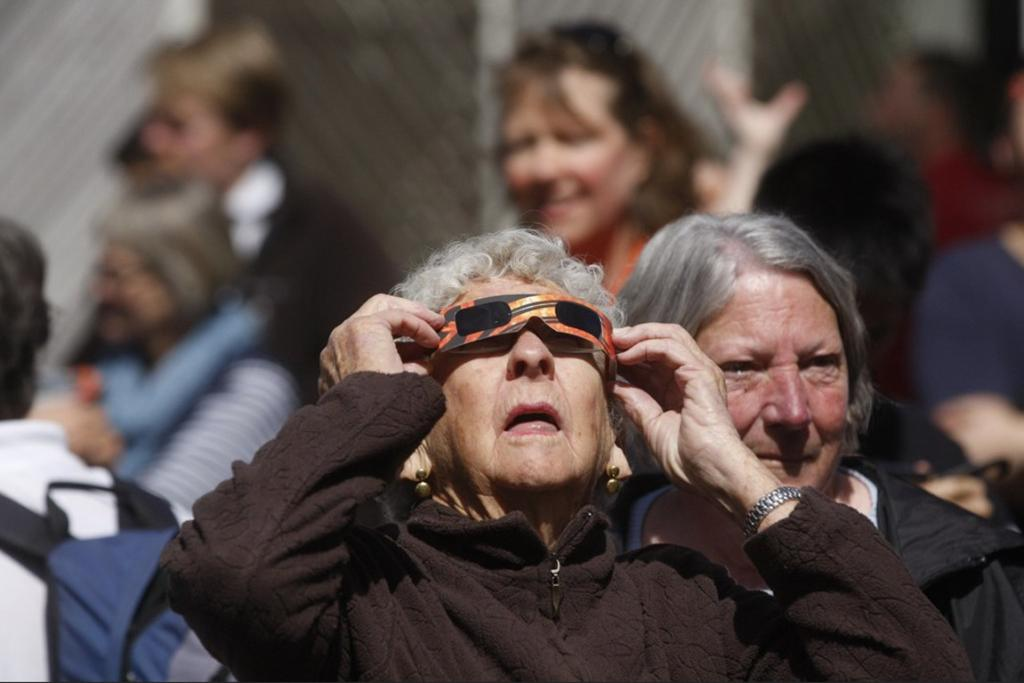 A woman attempts to view the eclipse through a special pair of viewing glasses.