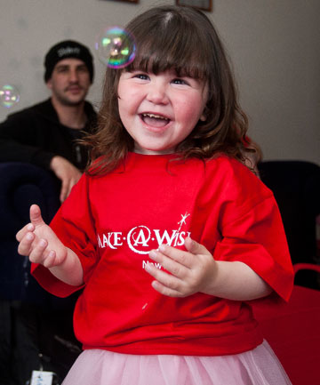 WISH COMES TRUE: Lilly Thoresen-McKay, 3, opens her presents that she received from the Make-a-Wish Foundation.