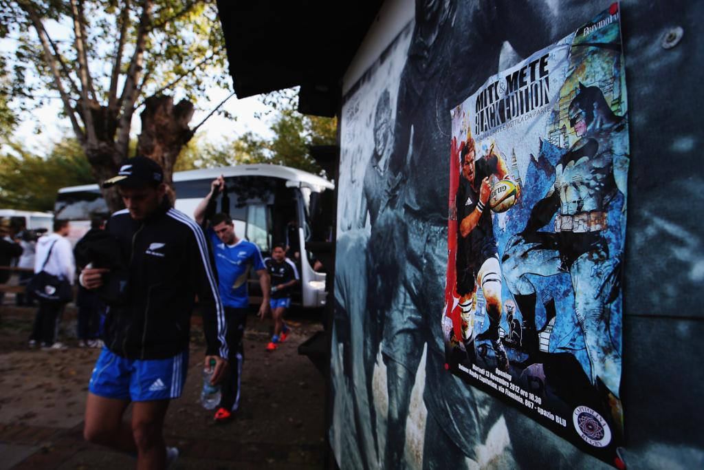 All Blacks players walk past a poster featuring Richie McCaw.