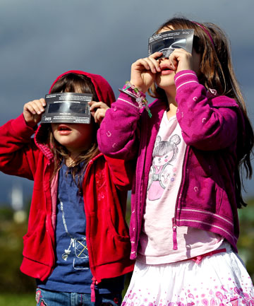 Rebecca, 4, and Alison Greenfield, 6, from New Plymouth, view Wednesday's eclipse