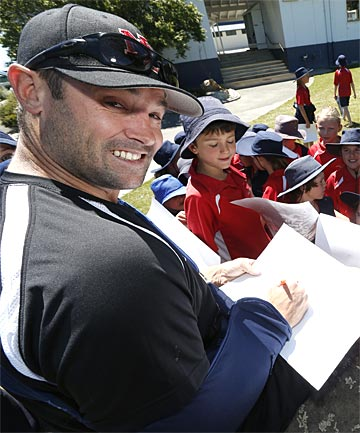 FIELDING REQUESTS: Black Sox member Rhys Casley signs his autograph for children at Clifton Terrace School.
