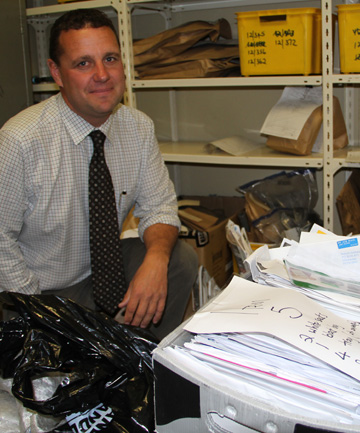Detective Grant Miller with some of the thousands of undelivered mail items found at the home of a NZ Post worker.