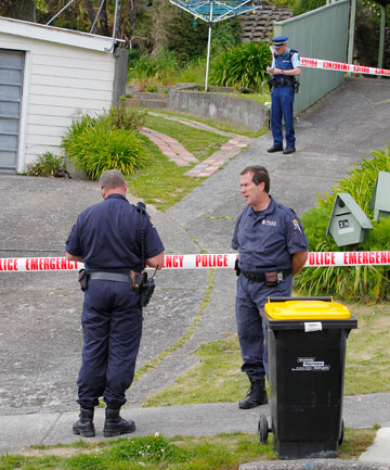 Police examine the Tawa property where a 33-year-old woman was found dead.