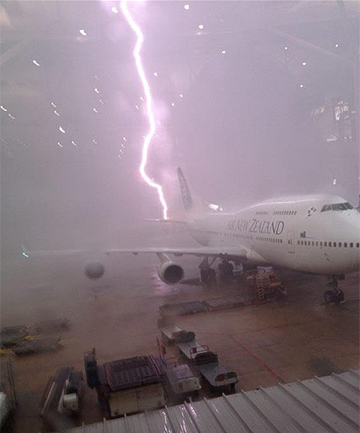 BANG: : A lightning bolt strikes behind an Air New Zealand plane in Brisbane yesterday.