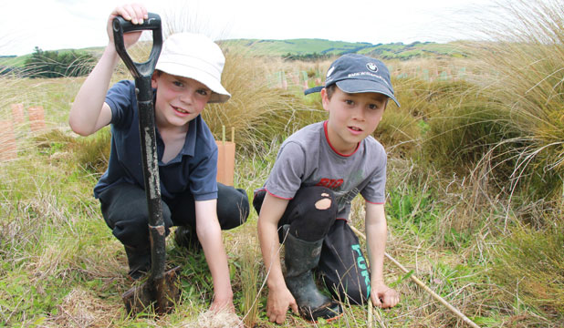 Robert Pullar and Joshua Potter, both 9, from Pukerau Primary School plant tussocks at the Pukerau Red Tussock Reserve as part of the Enviroschools Programme and the school's commitment to the community.
