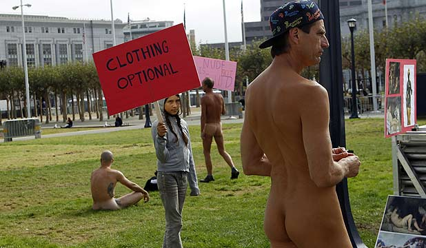 Inti Gonzalez carries a sign near nude men at Civic Center Plaza in San Francisco, California.