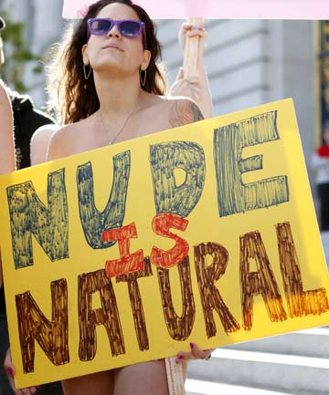 "A woman holds a sign saying ""Nude is Natural,"" during a rally against banning nudity in parts of the city in San Francisco, California."