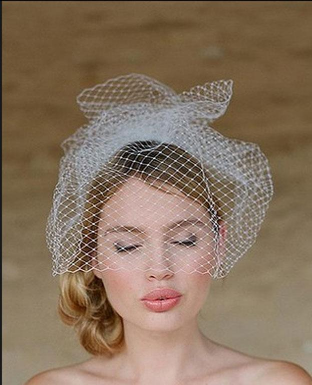 Go for an old-school vintage look with a short lace veil and a soft bun at the side.
