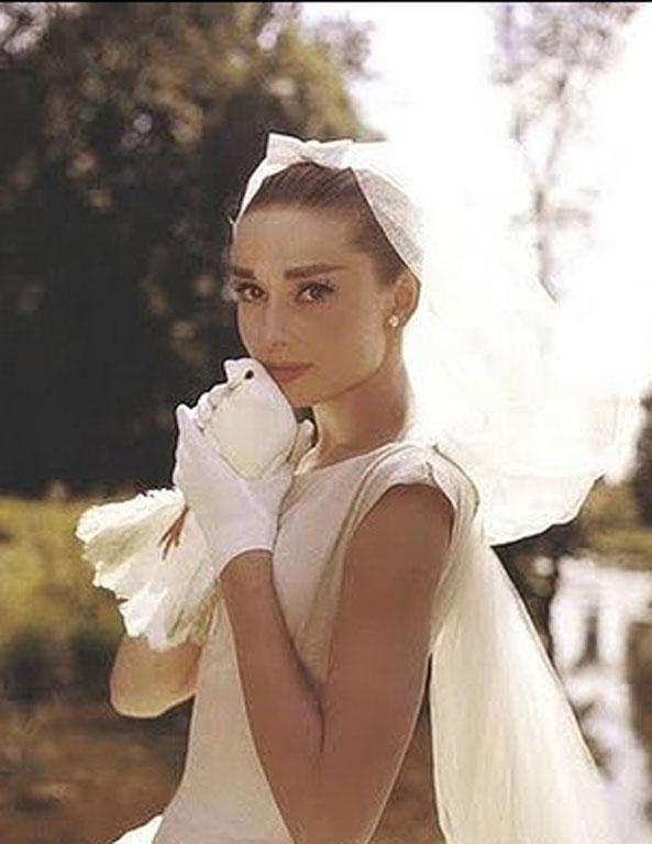 Behold: Audrey Hepburn with a dove. It's not in her hair per se, but it is close to it.