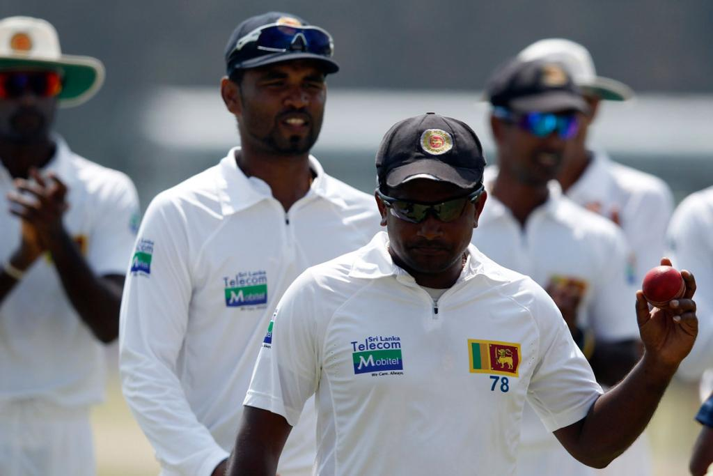 Sri Lanka's Rangana Herath (front) holds up the ball as he celebrates taking five wickets during the third day of their first test cricket match against New Zealand in Galle.