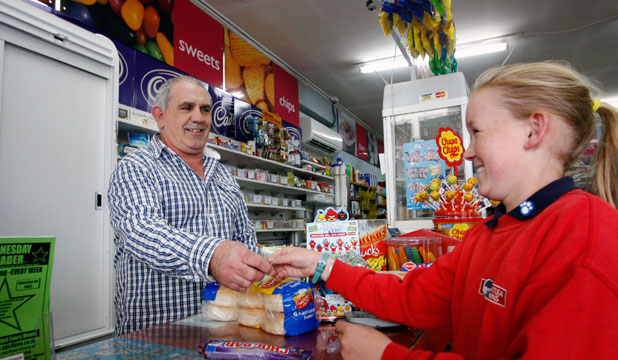 Olivia Milne buys a chocolate bar from dairy owner Grant Stevenson.