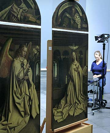 A restorer inspects some of the 24 framed panels of the Altarpiece or Adoration of the Mystic Lamb at The Genth Museum of Fine Arts.