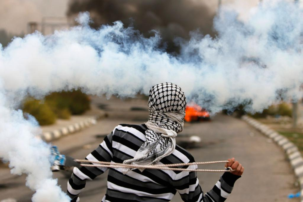 A Palestinian stone-thrower uses a sling to throw back a tear gas canister fired by Israeli security forces. The clashes broke out following a protest against Israel's military operation in the Gaza Strip.