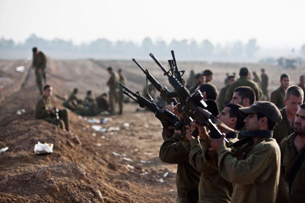 Israeli soldiers check their weapons at a staging area near the border with the Gaza Strip.