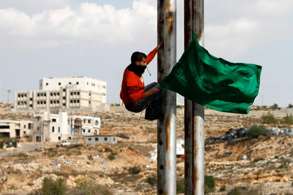 Palestinian stone-throwers holds a Hamas flag as he climbs a street pole during clashes with Israeli security forces. The clashes broke out following a protest against Israel's military operation in the Gaza Strip.