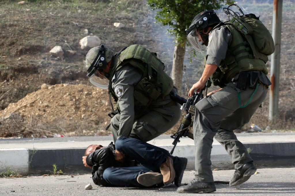 Israeli border policemen detain a Palestinian stone-thrower during clashes against Israel's military operation in the Gaza Strip.