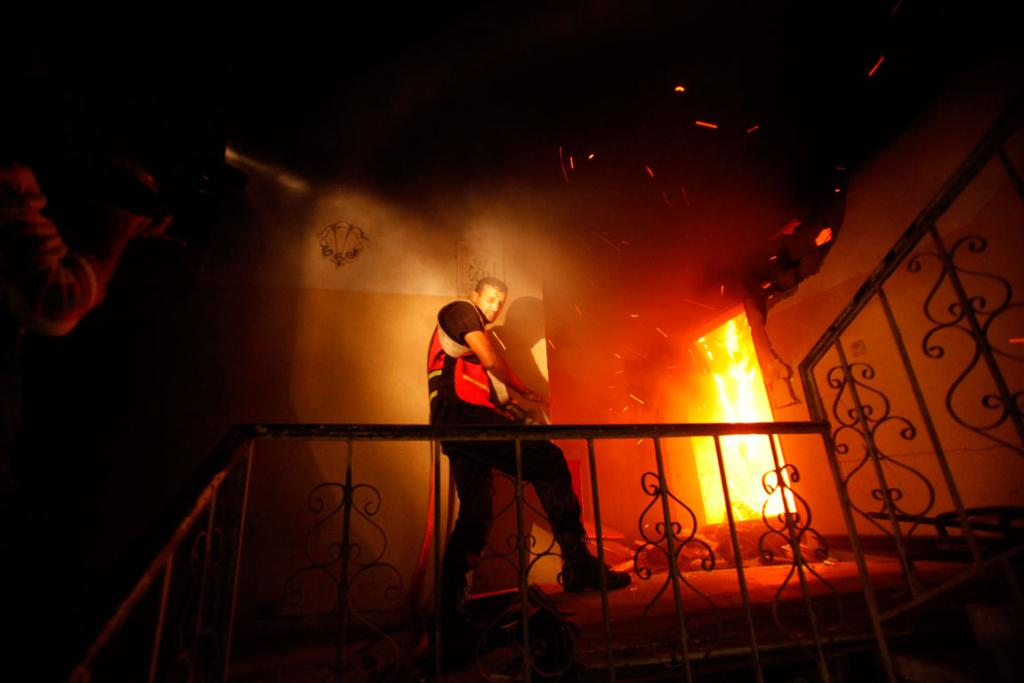 A Palestinian firefighter tries to extinguish a fire after an Israeli air strike.