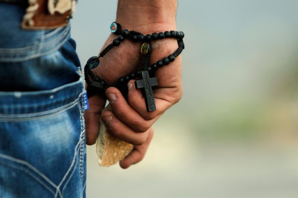 A Palestinian demonstrator wearing a rosary holds a stone during minor clashes with Israeli troops in protest against Israel's military operation in the Gaza Strip.