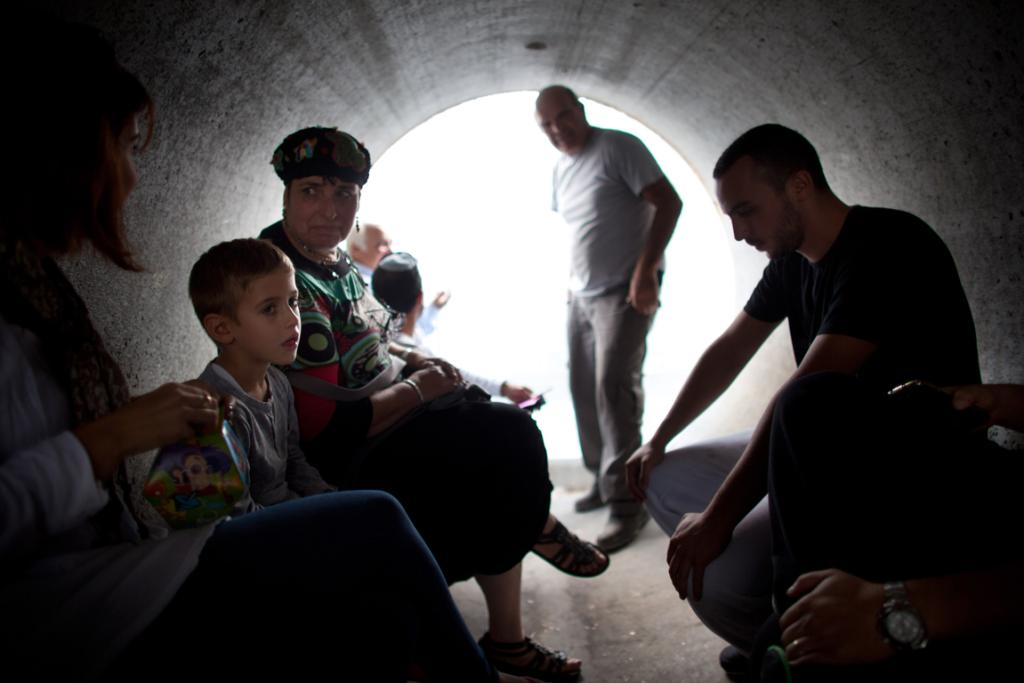 Israelis take cover in a large concrete pipe used as a bomb shelter during a rocket attack from the Gaza Strip.