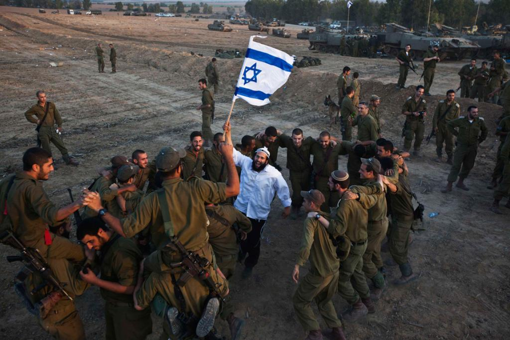A Hasidic Jewish man holds an Israeli flag as he dances with Israeli troops during a visit to support the soldiers, near the border with the Gaza Strip.