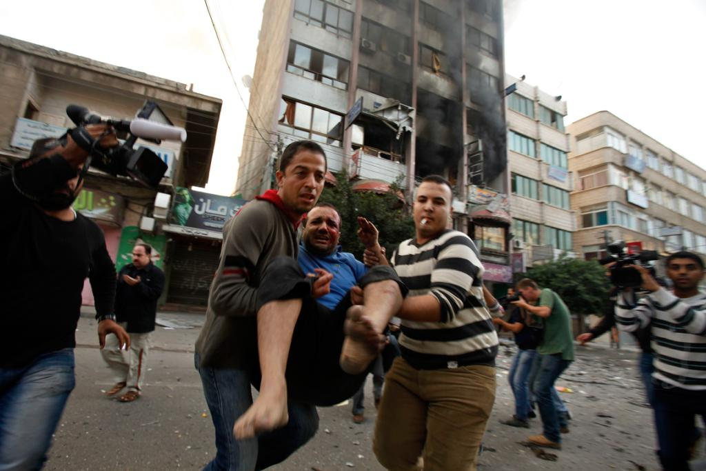 Palestinians evacuate a wounded man after an Israeli air strike on a building that also houses international media offices in Gaza City.