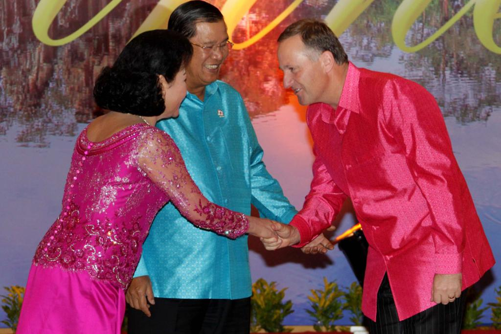 New Zealand Prime Minister John Key pictured in a pink shirt meets the Prime Minister of Cambodia, Hun Sen and his wife, Bun Rany Hun Sen.