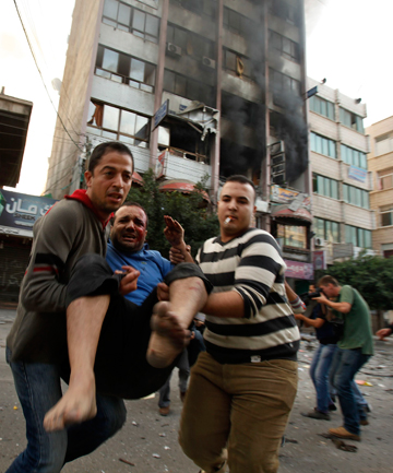 RESCUE: An injured man is rushed away from the scene of a bomb in Gaza City.