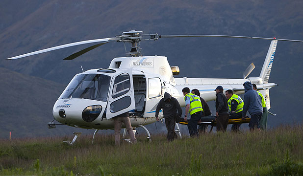 FLIGHT TO HOSPITAL: An injured paraglider is loaded onto a helicopter to take him to Queenstown Hospital.