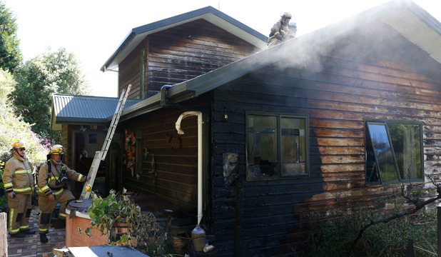 BURNOUT: Fire fighters attend to a house fire at Bill and Lyn Broughton's home in Wakapuaka.