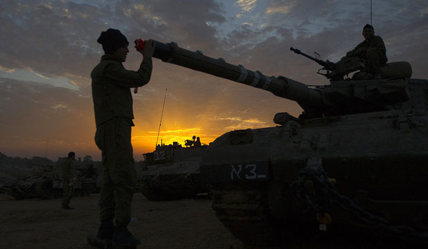 READY, AT EASE: An Israeli soldier adjusts the barrel of a tank at a staging area outside the Gaza Strip.