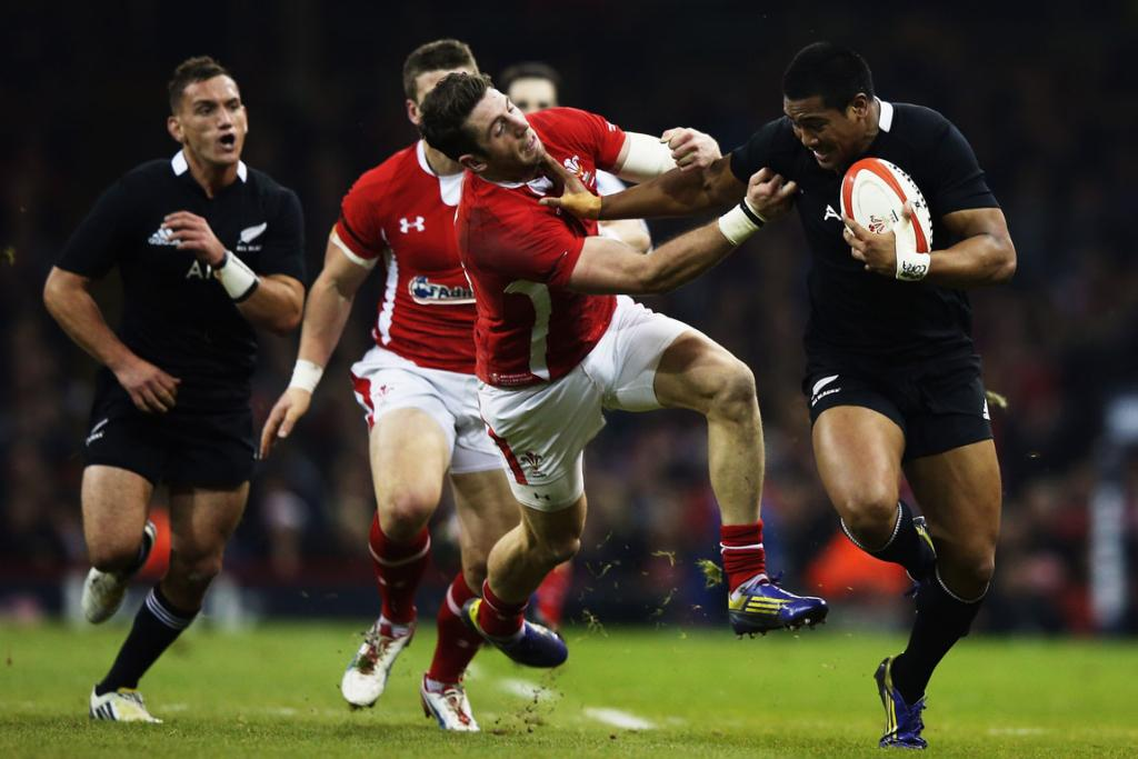 Julian Savea fends off the tackle by Wales' Alex Cuthbert.