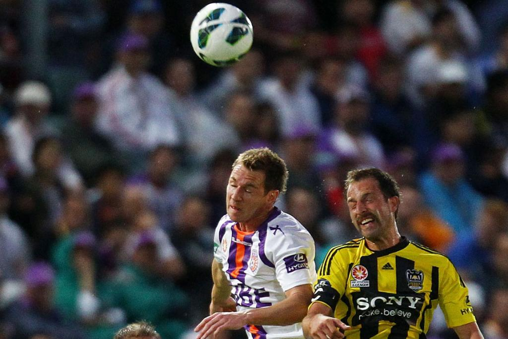 Shane Smeltz of the Glory and Andrew Durante of Wellington contest possession.