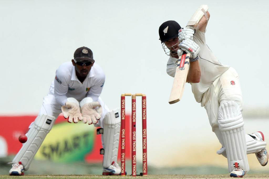 New Zealand cricketer Kane Williamson (R) is watched by Sri Lankan wicketkeeper Prasanna Jayawardene as he plays a shot during the first day of the second and final Test match.