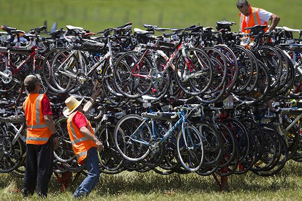 Event volunteers help sort racks of cycles ready for transport to relay transition points.