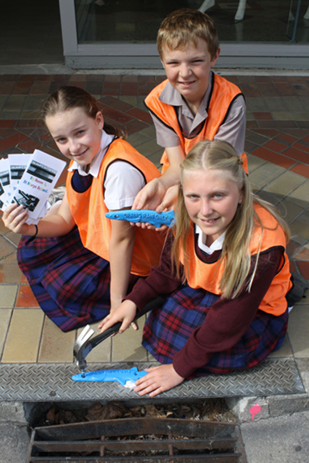 Clean Water: (Clockwise from left) Mackenzie Dawson, 11, Cade Vercoe, 11, and Emily Dalton, 11 from St Mary's School hammer in the plaques on Charles St reminding people not to dump pollutants down the drain