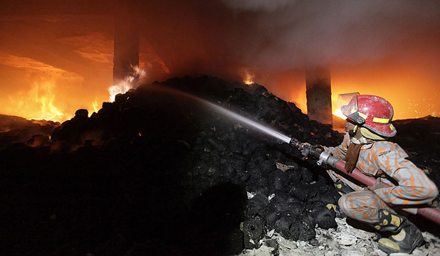 WORKERS TRAPPED IN BLAZE: A firefighter tries to control a fire at a garment factory on the outskirts of Dhaka. Score of people were killed in the blaze.