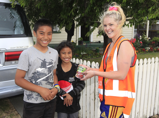 Manase Taufa, 10 and Lesieli Taufa, 8 donate to volunteer Jacqueline Williams.