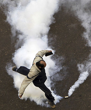 BACK IN THE STREETS: A protester tries to kick away a tear gas canister in Cairo.