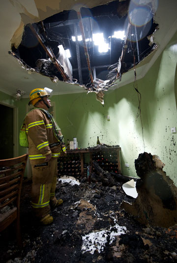 INCOMING: A firefighter stands under a hole blasted through the roof of a house in Berwick by a lightning strike.