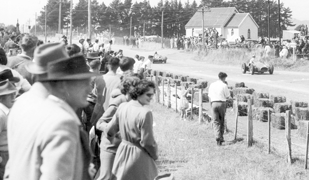 The huge crowd watches the flying racers from behind straw bales. Photo: Southland Museum.