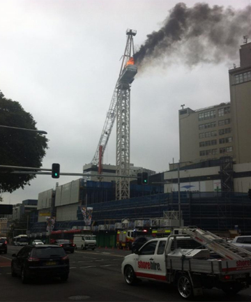 BURNING: The crane just after it collapsed.