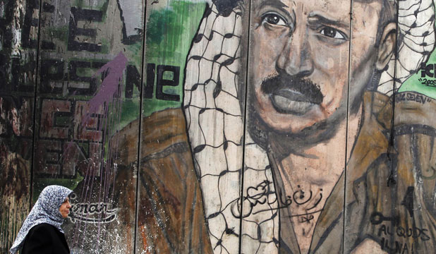 CAUSE DEATH UNKNOWN: A Palestinian woman walks past a mural on the controversial Israeli barrier depicting the late Palestinian leader Yasser Arafat.