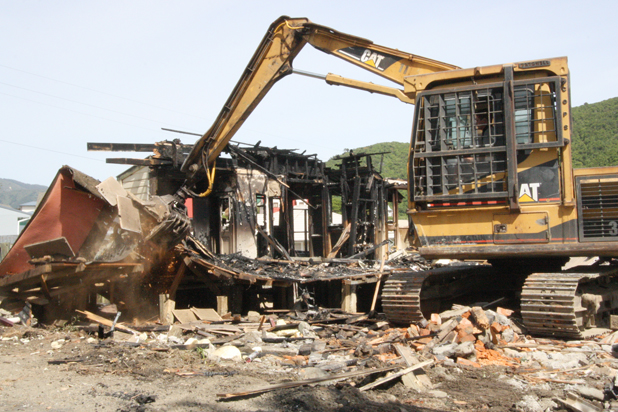 Going, gone: A digger contracted to Crafar Crouch Construction rips up the 1920s villa in Picton badly damaged by fire on Sunday morning.