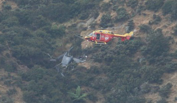 An emergency response helicopter hovers near the crash site of an air force Iroquois on Anzac Day 2010.